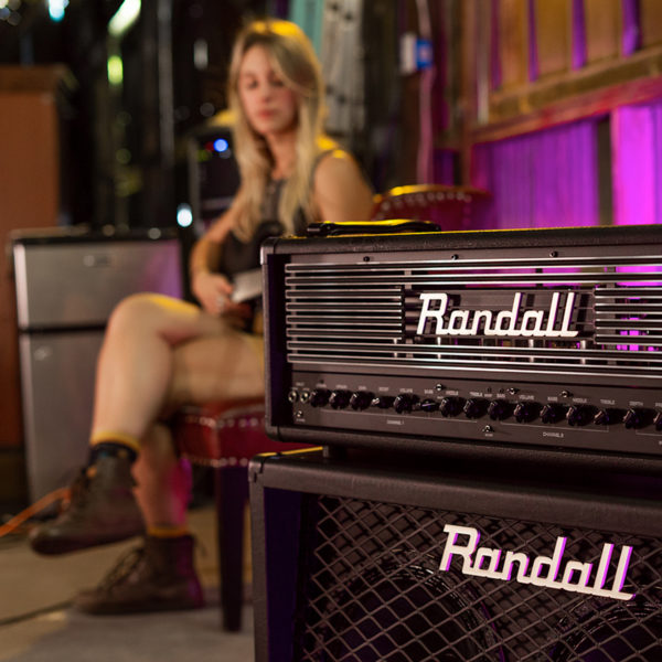 Randall Thrasher Tube Amplifier with woman playing electric guitar in background
