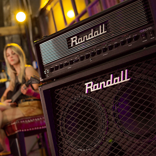 Randall amplifier and amplifier head with woman playing electric guitar in background