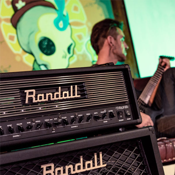 Randall cabinet and Thrasher Tube Amplifier with man playing electric guitar in background