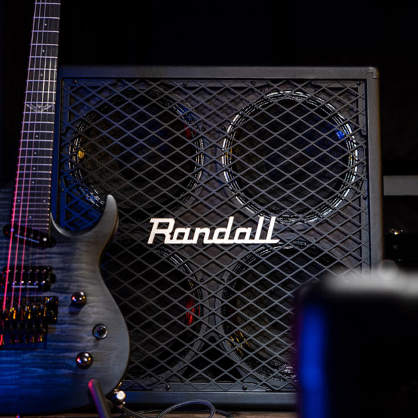 partial view of electric guitar in front of Randall cabinet